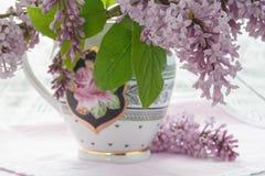 El florero con un ramo de primavera púrpura de la lila florece en te del vintage Imagen de archivo
