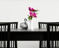El florero de la flor y la plata tallan el cisne de la estatua en una tabla Fotos de archivo libres de regalías