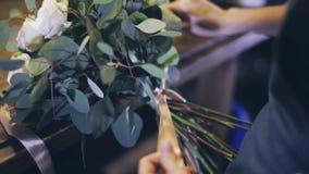 El florista anuda un arco en un ramo en una floristería metrajes