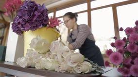 El florista de la mujer interrumpe las hojas en los troncos de rosas blancas largas entre las flores almacen de video