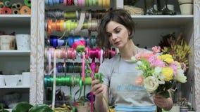 El florista de la mujer joven monta un ramo en una floristería