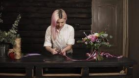 El florista de la mujer termina la composición del ramo, cortó las extremidades de las cintas de seda con las tijeras Excitado de almacen de metraje de vídeo