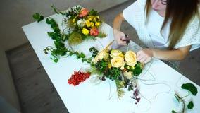El florista de sexo femenino hace el ramo floral grande de rosas con las herramientas, sentándose en oficina en d3ia n metrajes