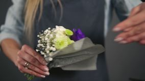 El florista de sexo femenino joven prepara un ramo de flores para la venta a los clientes Diseño floral, artes florales, creando  metrajes