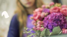 El florista hace el ramo de las flores Ramo de flores mezcladas hermosas en mano de la mujer almacen de video