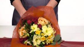 El florista hace un abrigo para las flores del ramo blanco Cámara lenta Cierre para arriba metrajes