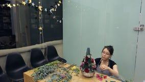 El florista moreno hace el arreglo floral en la tabla dentro de la oficina metrajes