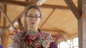 El florista talentoso crea el ramo floral que se coloca dentro metrajes