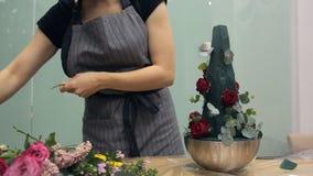 El florista trae el ramo floral de flores para la composición florística almacen de metraje de vídeo