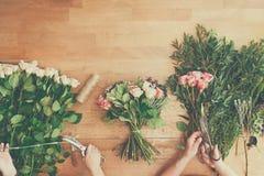 El florista y el ayudante en entrega de la floristería hacen el ramo color de rosa, opinión de sobremesa Imagen de archivo