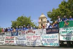 El flotador de un equipo de béisbol de la liga pequeña con los anuncios del patrocinador hace su calle principal de la manera aba Fotos de archivo libres de regalías