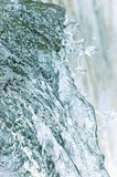El fluir de la cascada de la cascada del agua salpica el fondo, primer vertical detallado grande, azul brillante, colores en colo fotos de archivo