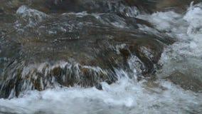 El fluir del agua golpeado la roca y la onda que salpican en el río metrajes