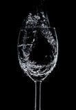 El fluir del agua que llena en las copas de vino fotos de archivo