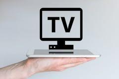 El fluir del vídeo y concepto de Internet TV con el teléfono o la tableta elegante Fotos de archivo libres de regalías