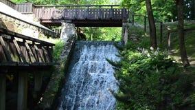 El flujo de corriente del arroyo funciona con la cascada retra vieja del puente del molino de agua almacen de video