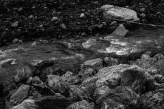 El flujo r?pido de un r?o de la monta?a con las piedras imagenes de archivo