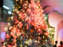 El foco borroso en el árbol de navidad rojo con los decoros ligeros Imágenes de archivo libres de regalías