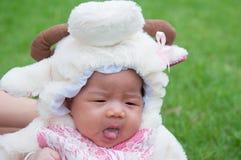 El foco en el bebé recién nacido asiático con las pequeñas ovejas de los trajes en el jardín y la madre la está deteniendo Imagen de archivo libre de regalías