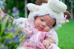 El foco en el bebé recién nacido asiático con las pequeñas ovejas de los trajes en el jardín y la madre la está deteniendo Foto de archivo