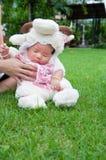 El foco en el bebé recién nacido asiático con las pequeñas ovejas de los trajes en el jardín y la madre la está deteniendo Imagen de archivo