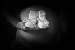 El foco en la mujer embarazada está sosteniendo calcetines recién nacidos de una muchacha con la cinta Imagen de archivo