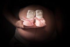 El foco en la mujer embarazada está sosteniendo calcetines recién nacidos de una muchacha con la cinta Imágenes de archivo libres de regalías