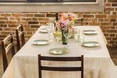 el foco selectivo de la tabla sirvió con las copas de vino, las placas vacías y la botella de vino imágenes de archivo libres de regalías