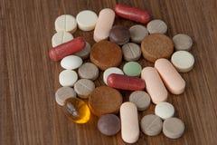 El foco selectivo en píldora se separó en fondo de madera concepto global de la atención sanitaria Industria farmacéutica Drogas  imagen de archivo libre de regalías