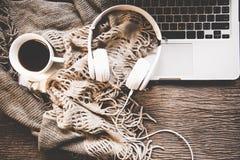 El fondo acogedor del invierno, la taza de café caliente con la melcocha y la música del auricular, calientan el suéter hecho pun fotos de archivo libres de regalías