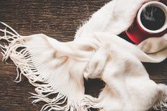 El fondo acogedor del invierno, taza de café caliente con la melcocha, calienta el suéter hecho punto en el viejo fondo de madera Fotos de archivo libres de regalías