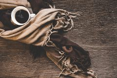 El fondo acogedor del invierno, taza de café caliente con la melcocha, calienta el suéter hecho punto en el viejo fondo de madera Foto de archivo libre de regalías