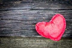 El fondo bajo la forma de corazón rojo del corazón en el piso de madera Fotos de archivo