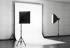 El fondo blanco se encendió con el equipo del estudio contra una pared de ladrillo Imagenes de archivo
