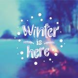 El fondo borroso con el fuego ardiente en nieve y dibujado con invierno del texto de la tiza está aquí stock de ilustración