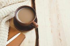 El fondo casero del invierno acogedor, taza de cacao caliente, cuaderno y calienta el suéter hecho punto en fondo de madera liger Imagen de archivo libre de regalías