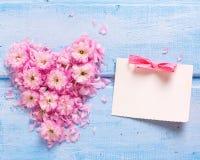 El fondo con el corazón de las flores rosadas y los pétalos y vacian Imagen de archivo