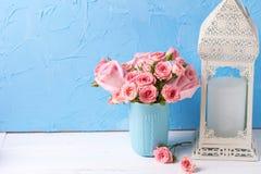 El fondo con las rosas rosadas florece en taza azul y el lanter blanco Imagen de archivo libre de regalías