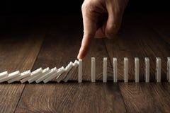 El fondo creativo, la mano de los hombres par? efecto de domin?, sobre un fondo de madera marr?n Concepto de efecto de domin? imagen de archivo