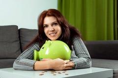 El fondo creativo, una muchacha hermosa abraza una hucha bajo la forma de cerdo verde El concepto de dinero de ahorro, ahorros, c foto de archivo libre de regalías