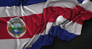 El fondo 3D de Costa Rica Flag Wrinkled On Dark rinde Imagenes de archivo