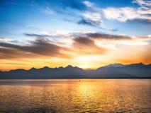 El fondo de la naturaleza con el mar y los mountanes ajardinan en la puesta del sol Imágenes de archivo libres de regalías