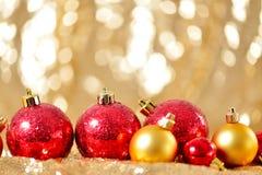 El fondo de la Navidad, el cierre del Año Nuevo encima del rojo y las bolas de la decoración del oro en extracto del brillo empañ Imagenes de archivo