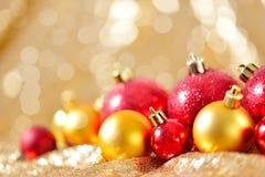El fondo de la Navidad, el cierre del Año Nuevo encima del rojo y las bolas de la decoración del oro en extracto del brillo empañ Imagen de archivo libre de regalías