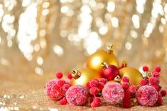 El fondo de la Navidad, el cierre del Año Nuevo encima del rojo y las bolas de la decoración del oro en extracto del brillo empañ Fotos de archivo