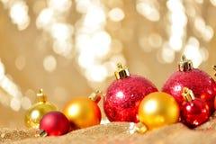 El fondo de la Navidad, el cierre del Año Nuevo encima del rojo y las bolas de la decoración del oro en extracto del brillo empañ Fotos de archivo libres de regalías