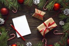 El fondo de la Navidad con el cuaderno en blanco, abeto ramifica, decorati Imagenes de archivo