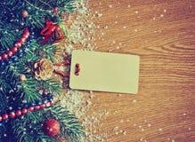 El fondo de la Navidad con el abeto ramifica, las campanas, etiqueta de papel Fotografía de archivo