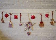 El fondo de la Navidad con la guirnalda de estrellas, regalo, conos del pino, las decoraciones rojas en fondo de madera con el ab Fotos de archivo libres de regalías