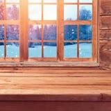 El fondo de la Navidad con la tabla vacía de madera sobre ventana y la naturaleza del invierno ajardinan Interior de la casa de v Fotografía de archivo